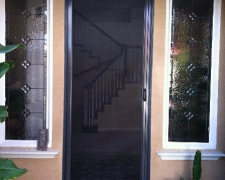 TALL BRONZE ROLL-AWAY DISAPPEARING SCREEN DOOR IN USE