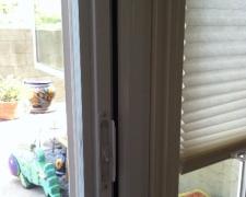 WHITE ROLL-AWAY SCREEN DOOR FLUSH WITH DOOR MOULDING ON DOOR THAT SWINGS OUT