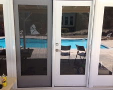 WHITE FRENCH ROLL-AWAY SCREEN DOORS WITH FIXED DOOR LOCKED IN PLACE